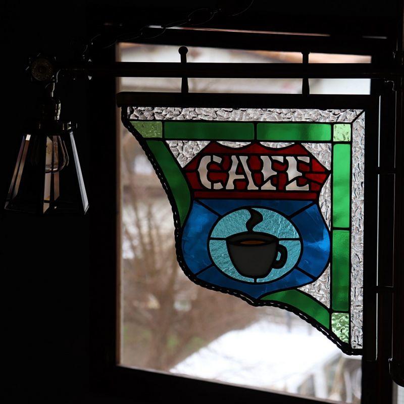 ステンドグラスのカフェサイン看板を眺めながら贅沢な時間を持つ、昼間は外の陽の光で見せるステンドグラス