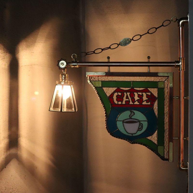 ステンドグラスのカフェサイン看板を眺めながら贅沢な時間を持つ、夜は照明の灯りで見せるステンドグラス